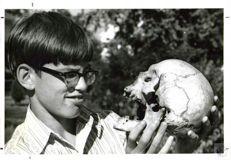 Image: di02637 - Tommy Turner, 13, looks at old Indian skull