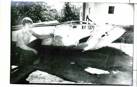 Image: di03799 - Todd True, 17, examines wrecked boat from which he rescued a friend