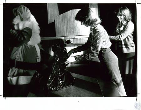 Image: di10074 - Pat Benigi (Santa) having baggage checked by security agents Susan Reineke and Debbie Caldwell