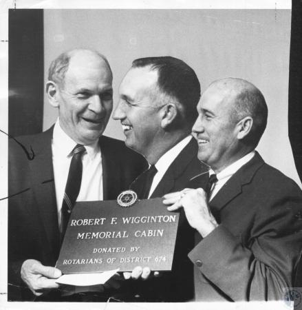 Image: di10715 - unknown members with plaque for Robert F. Wigginton Memorial Cabin