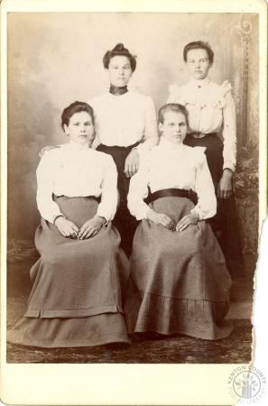 Image: di101587 - Four unidentified woman, two standing , two seated with white blouses and dark skirts