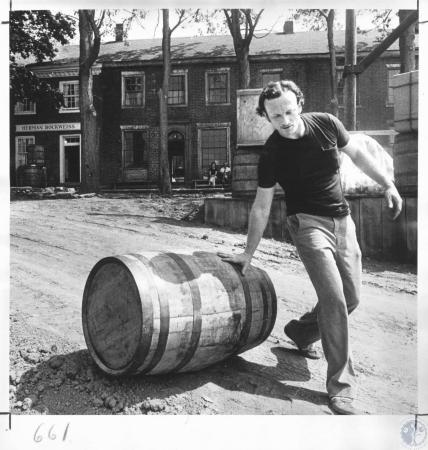 Image: di11185 - Ron Heuberger, stagehand, rolling barrel down dirt ramp to wharf - centennial