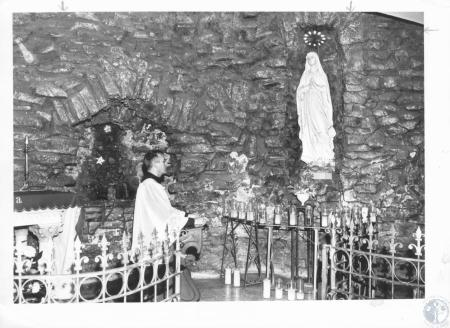 Image: di12246 - Rev. Raymond McClanahan kneels before statue of Mary in Grotto