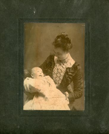 Image: di126398 - Unknown woman holding baby and smiling.