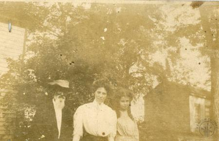 Image: di126452 - Unknown family standing in yard outside of houses.
