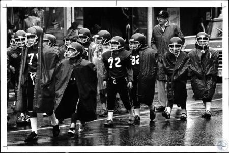 Image: di127971 - Coach Butch Caldwell (baseball hat) marches in pouring rain with his team