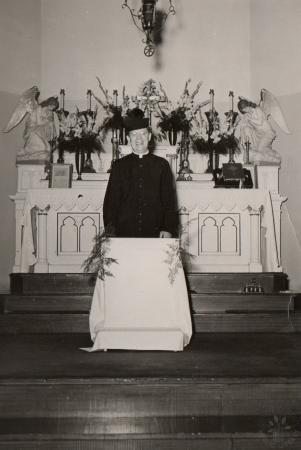 Image: di130021 - Fr. Jerome Heuermann in front of high alter, Saint John Church