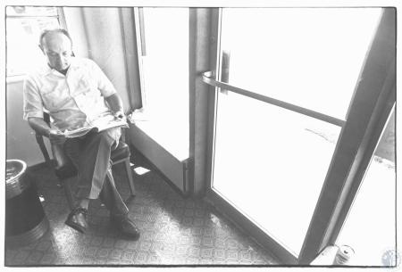 Image: di19210 - Wayne Jaggers reading paper during lull at his barber shop