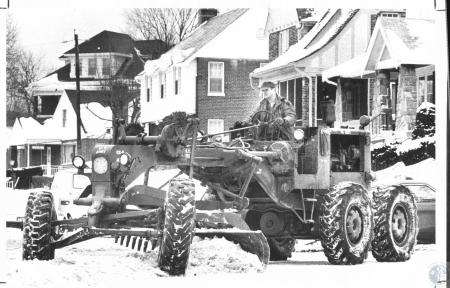 Image: di20663 - Lloyd Soard (36), Sgt. US Army Res., using a army grader to clear the intersection of Electric Ave and....
