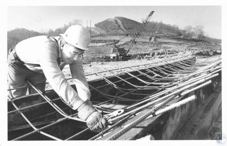 Image: di20928 - Bert Spivey wiring reinforcement steel together into a form for a concrete drainage ditch at the I-175....