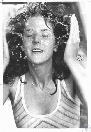 Image: di22116 - Carol McCormick (19) cooling off at a faucet after a hot day at the races
