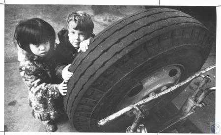 Image: di22446 - Eileen Palad (4) and Kristian Klaene (3) examining bus tire