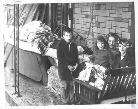 Image: di23225 - Four Wright Children, Randy (10), Janice (8), Carol (19) and Cynthia (20) huddle on the front porch of....