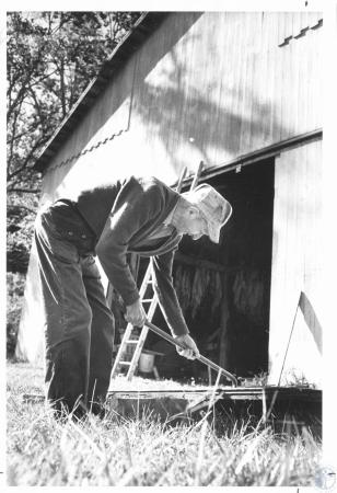 Image: di23272 - Clyde Young (78), fixing door hinges on the bard, using a crow bar