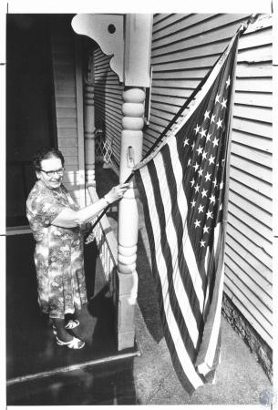 Image: di23274 - Helen Young (74) putting flag on her front porch