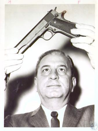 Image: di27221 - Detective Pat Ciafardini examining pistol