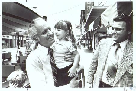Image: di31472 - Gov. Julian Carroll holding Michell Ishmael (3), Joe Battaglia, Covington police detective, guarding....