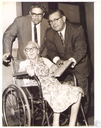 Image: di32036 - Lida Weddle, in wheel chair, Howell Vincent, and James Weddle, her son, just before Lida's $15,000 damage....