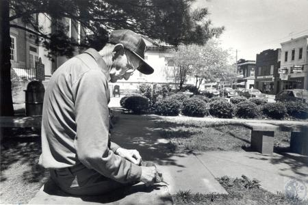 Image: di40278 - Gordon Robinson (79) sharpening his knife in front of the Grant County Courthouse