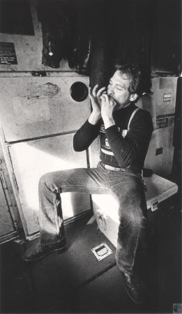 Image: di43287 - Joe Carey passes time on trip to Danville playing harmonica