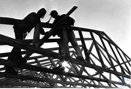 Image: di48319 - Pair of workmen nail roof trusswork into place, Doug Arbogast, left, and Jack Hendrix, right, both of....