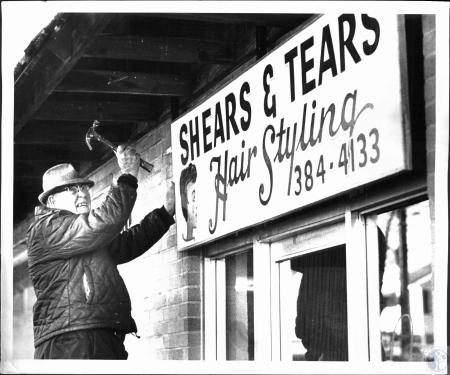 Image: di53864 - Elmer Meyer hangs sign he painting for Shears and Tears Hair Styling at Hathawy and US 42