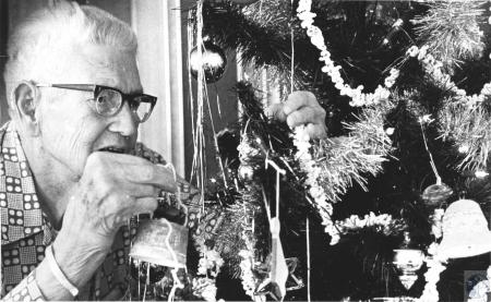 Image: di57605 - Herbert Angel (83), adding Christmas ornament to tree at Woodspoint Nursing Home