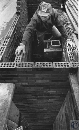 Image: di60303 - Ray Barton (44) laying brick for fireplace chimney for new addition to Gatehosue Tavern at Drawbridge....