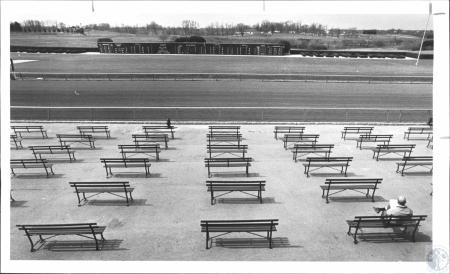 Image: di61150 - A man who got there as athe gates opened has the benches all to himself as he checks his racing form....