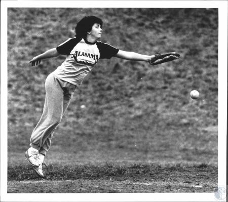 Image: di61643 - Donna Powell makes a stab at a ball to left field during softball practice at Holmes High School.