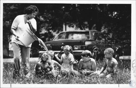 Image: di63083 - Vivian Ludwick pours water on kids at Elsmere Day Care Center. The Center had no air conditioning.