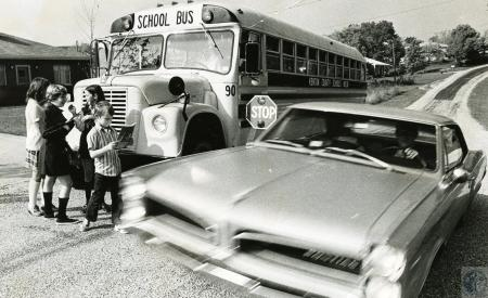 Image: di66785 - Car passes parked school bus. Children in picture are Tommy Jones, Melissa Gibson, Linda Sayers and Kathy....