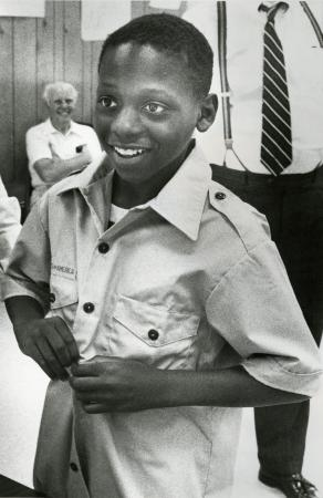 Image: di71305 - Deon Gary (12), 6th grader at John G. Carlisle, tries on shirt Ida Spence Boy Scouts.