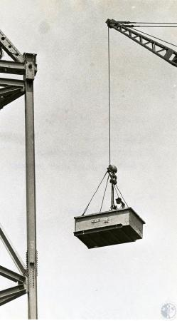 Image: di73162 - Unidentified riding along with equipment being moved by crane.
