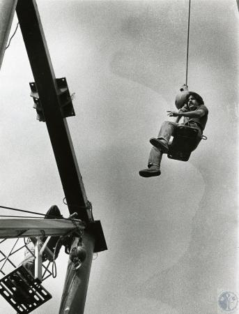 Image: di73172 - Unidentified laborer getting a lift to job site from crane.
