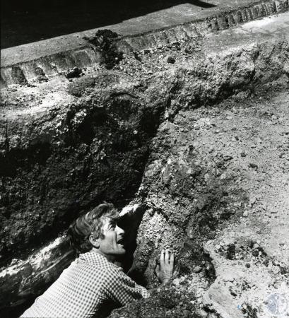 Image: di73178 - Unidentified worker in hole below street level.