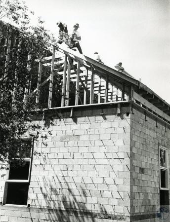 Image: di73199 - Unidentified workers installing roof on building.