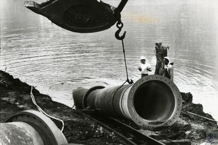Image: di73744 - Unidentified laborers directing crane with large pipe.