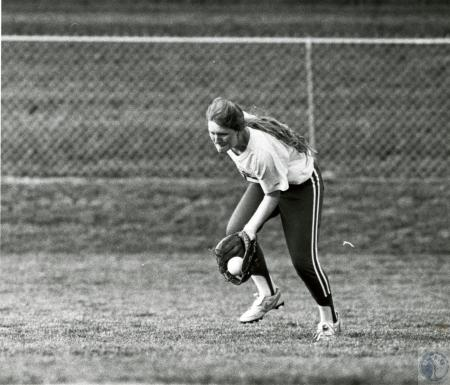 Image: di74585 - Unidentified female softball player fielding grounder in the outfield.