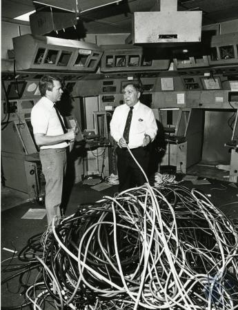 Image: di74938 - Don Barker of the Airway Facilities Office, and San Juan Romero, air traffic manager of GCIA, look over....