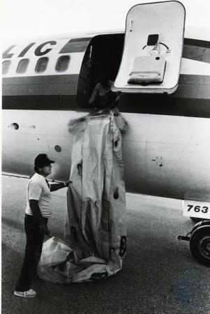 Image: di74976 - Chute that was busted and caused injuries being removed by unidentified workmen after Republic Flight....