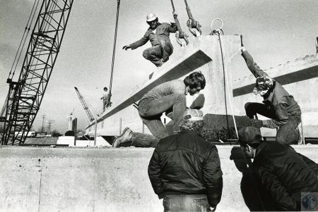 Image: di75431 - Unknown construction workers positioning concrete beams as other unidentified workers look on.