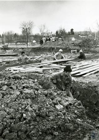 Image: di75472 - Unknown laborers working while unknown group in background meet.