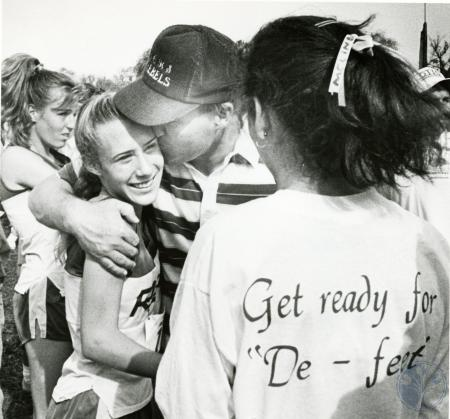 Image: di76222 - Unidentified Boone County High School female cross country runner receiving congratulatory hug and kiss....