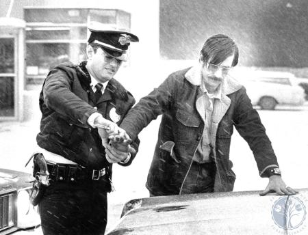 Image: di76376 - Covington Police Officer Terry Armstrong handcuffs Ronnie Steele, suspect in Bellevue armed robbery.