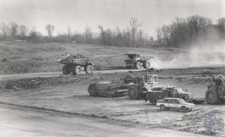 Image: di80370 - Two large trucks - off road pass - one with load and one empty - at airport runway project.