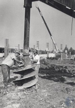 Image: di80438 - Construction workers are drilling holes for more supports like ones in background, for %15 million parking....