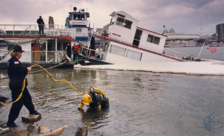 Image: di81304 - Boone-Kenton water rescue diver backs into water as he prepares to try to put a floatation device under....