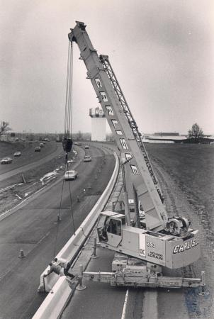 Image: di81636 - Carlisle heavy cran lifting concrete barriers in place on I-75 South. Two men directing barriers are....