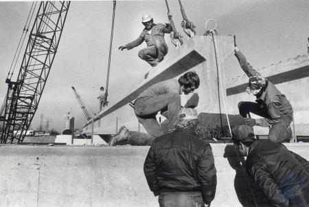 Image: di82883 - Unidentified construction workers setting concrete beam in place.